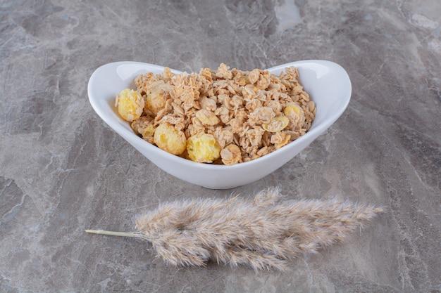 Een wit bord vol gezonde heerlijke cornflakes op grijze tafel.