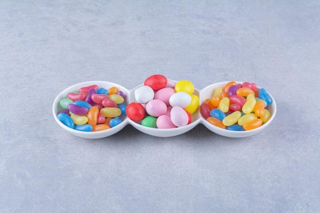 Een wit bord vol kleurrijke bonen snoepjes op grijze tafel.
