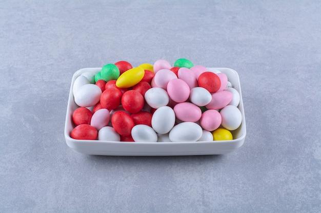 Een wit bord vol kleurrijke bonensnoepjes op een grijze ondergrond