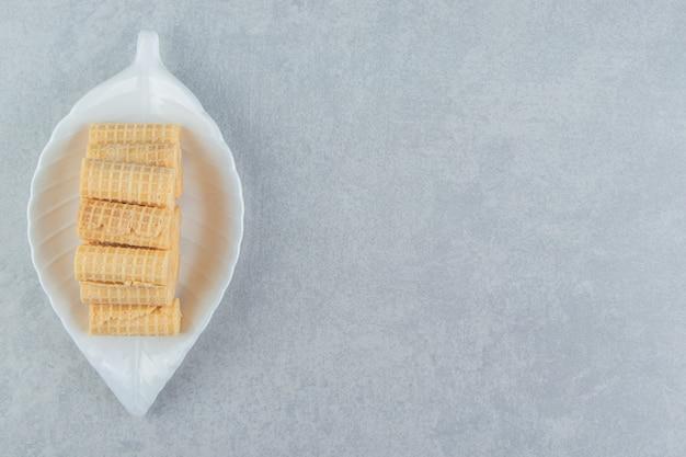 Een wit bord vol knapperige wafelbroodjes.