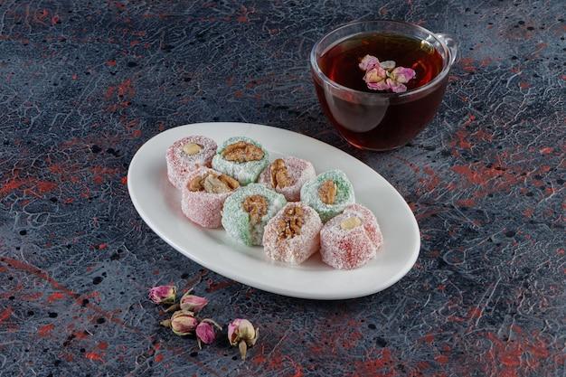 Een wit bord vol traditionele turkse lekkernijen met een glazen kop hete thee