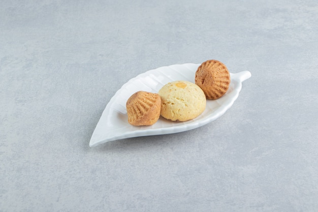 Een wit bord vol zoete heerlijke koekjes met suiker.