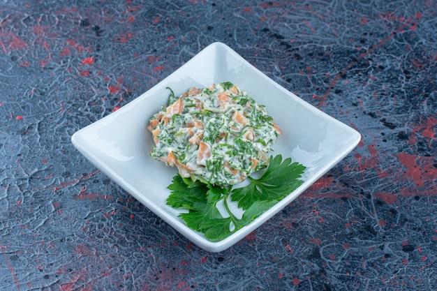 Een wit diep bord met heerlijke salade en kruiden