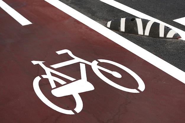 Een wit fietspadteken op een asfaltwegdek van een stad in de veiligheidszone voor fietsen op de voorgrond