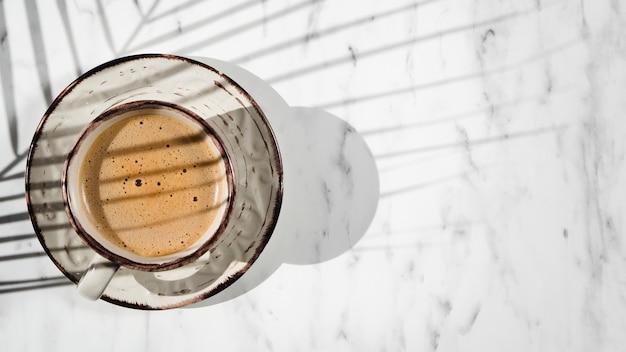 Een wit gevuld met koffiekopje op een witte achtergrond bedekt door een ficus blad schaduw
