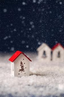 Een wit huisje met een rood dak op een blauwe achtergrond met sneeuw een wenskaart