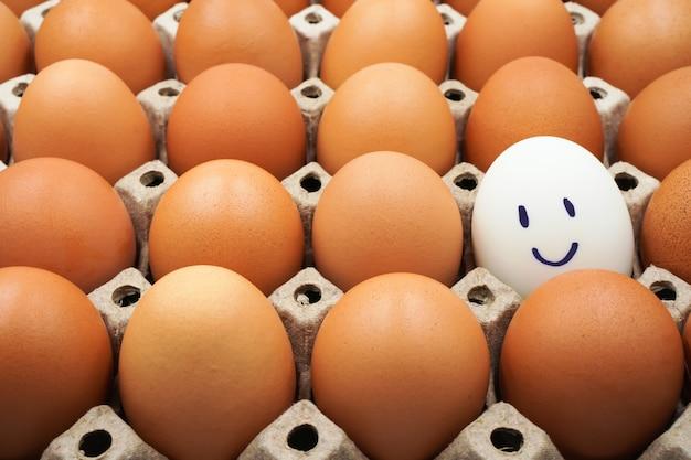 Een wit kippenei met blij en smileygezicht tussen bruine eieren in de doos