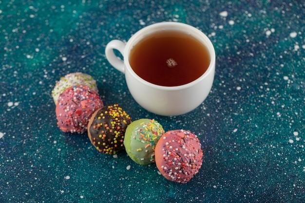 Een wit kopje thee met heerlijke kleine donuts.