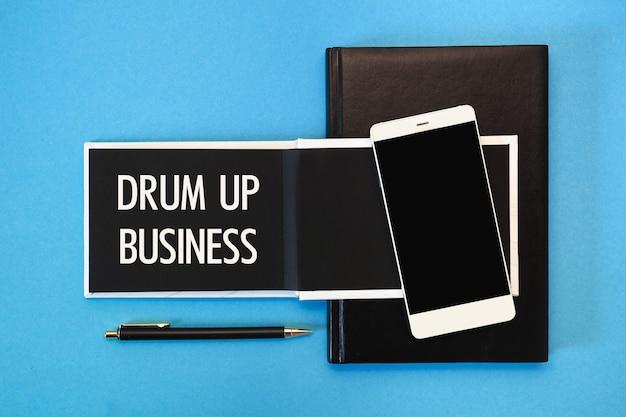 Een wit notitieboekje met zwarte pagina's, een smartphone en een pen op een blauwe achtergrond. de inscriptie drum up business op het kladblok.