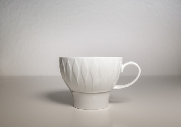 Een wit porseleinen kopje op een witte achtergrond