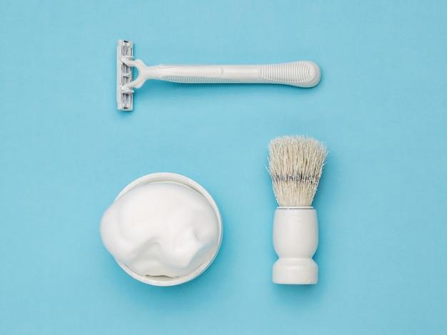 Een wit scheermes, een witte scheerkwast en een witte kom scheerschuim op een blauw oppervlak