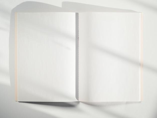 Een wit schetsboek op een witte achtergrond met schaduwen