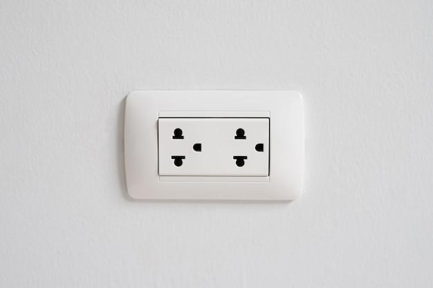 Een wit stopcontact aan de muur.