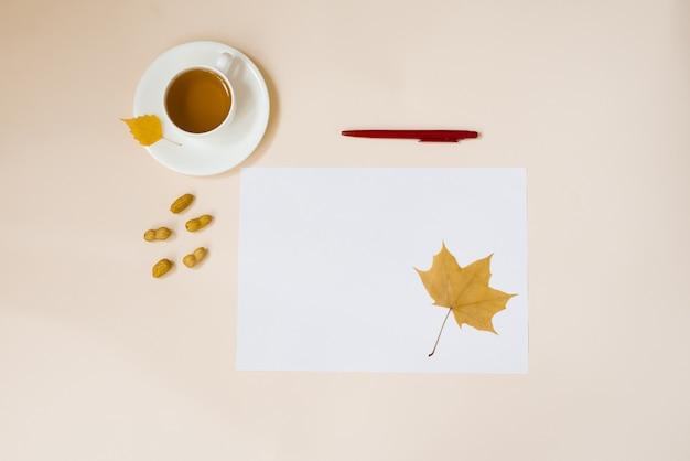 Een wit vel papier, een rode pen, herfstbladeren en een kopje hete thee op een beige achtergrond. kopieer ruimte