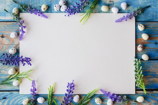 Een wit vel papier omlijst met paarse bloemen en kwarteleitjes op een versleten blauwe houten tafel