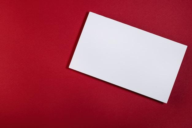 Een witte ansichtkaart op een rode achtergrond. een lege ruimte voor de tekst.