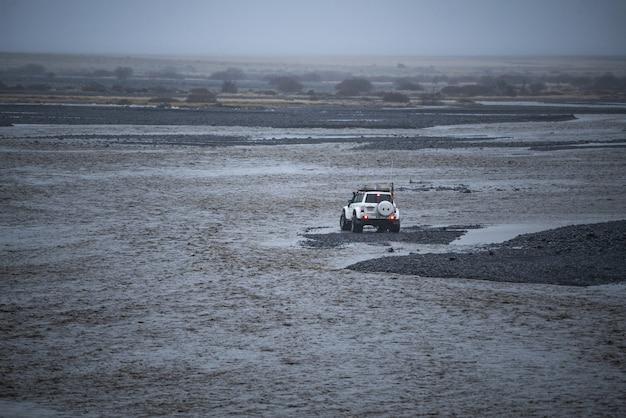Een witte auto die besluit de rivier over te steken