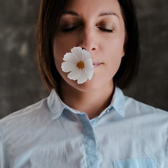 Een witte bloem in de mond van het meisje