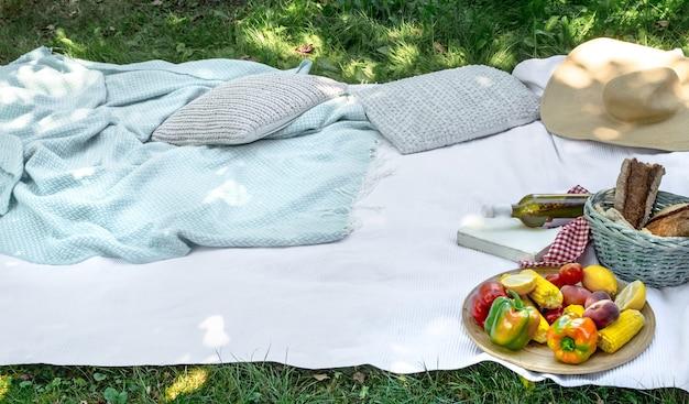 Een witte deken op het groene gras. het concept van een picknick.