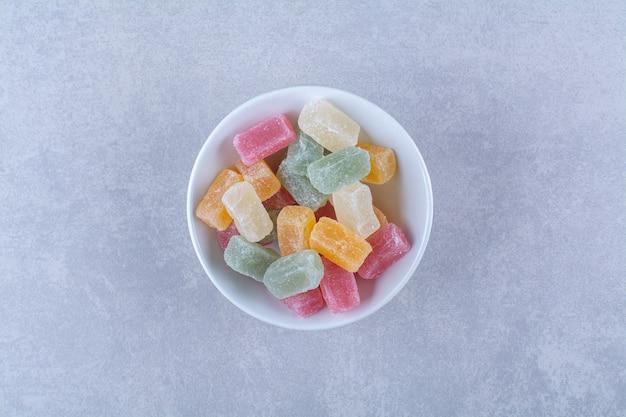 Een witte diepe plaat vol kleurrijke bonen snoepjes op grijze achtergrond. hoge kwaliteit foto