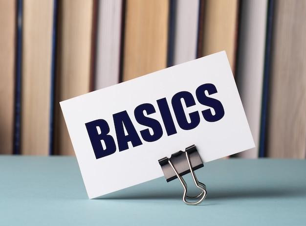 Een witte kaart met de tekst basics staat op een clip voor papieren op tafel tegen de achtergrond van boeken. defocus