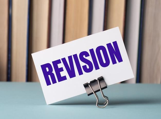 Een witte kaart met de tekst revision staat op een clip voor papieren op tafel tegen de achtergrond van boeken. defocus