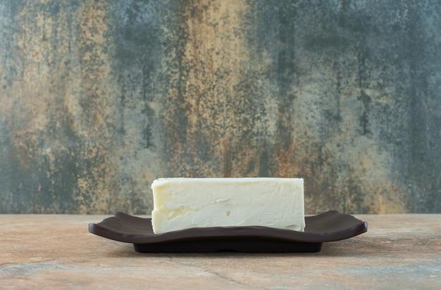 Een witte kaas op een donkere plaat op marmeren tafel.