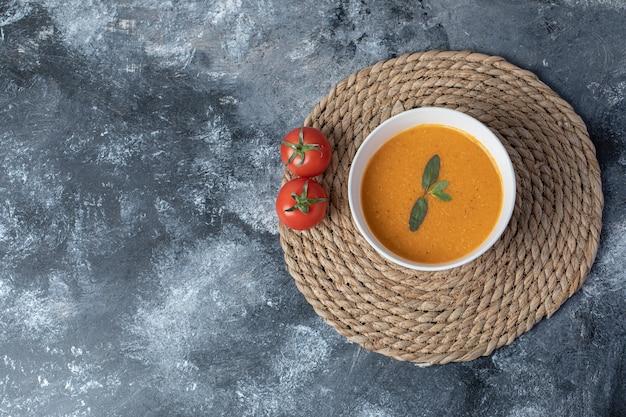 Een witte kom linzensoep met tomaten op een marmeren achtergrond.