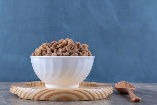 Een witte kom met gezonde chocoladegranenringen voor het ontbijt.