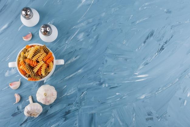 Een witte kom met veelkleurige rauwe spiraalvormige pasta met knoflook en kruiden.