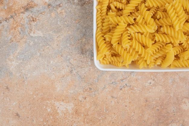 Een witte kom onvoorbereide macaroni op marmeren ruimte.