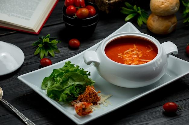 Een witte kom tomatensoep met gehakte parmezaanse kaas en groene salade.