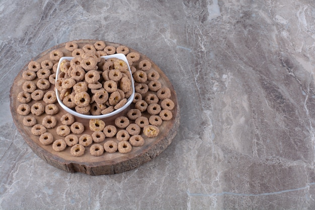Een witte kom vol gezonde chocoladegranenringen op een houten stuk.