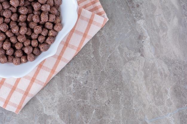 Een witte kom vol heerlijke chocolade maisballen op tafelkleed.