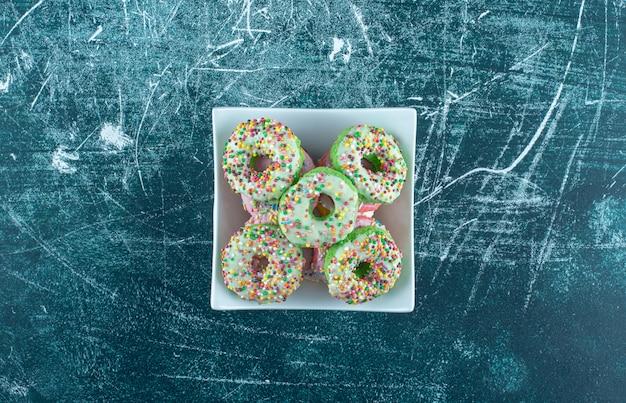 Een witte kom vol zoete donuts op een blauwe achtergrond. hoge kwaliteit foto