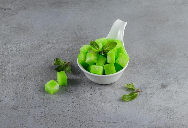 Een witte kom vol zoete groene snoepjes met muntblaadjes op een steen.