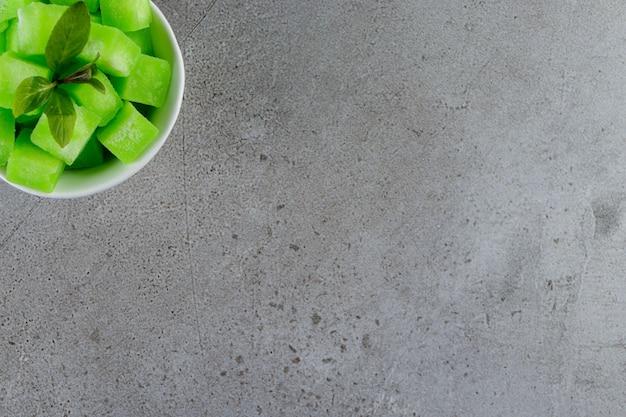 Een witte kom vol zoete groene snoepjes met muntblaadjes op een stenen tafel.