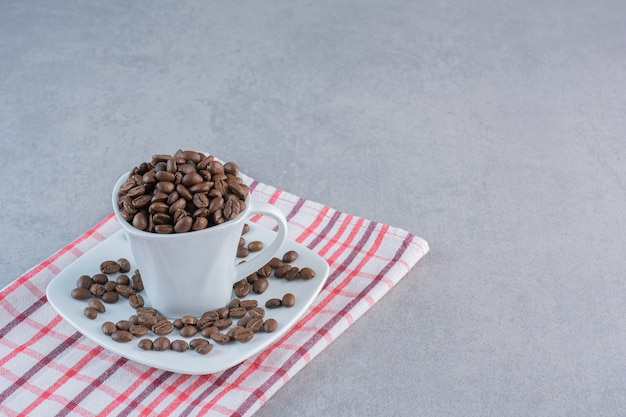 Een witte kop gebrande koffiebonen op gestreept tafelkleed.