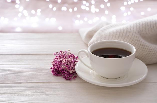 Een witte kop koffie, een boeket en een trui op de achtergrond van een brandende slinger. zijaanzicht met kopie ruimte. het concept van vakantieachtergronden.