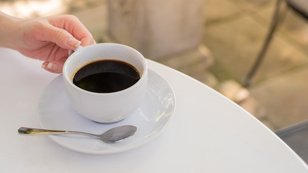 Een witte kop koffie op witte tafel met werkpauze. een glas hete espresso.