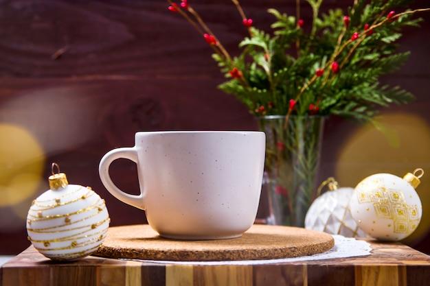 Een witte kop met een warme drank staat op een houten plank tussen witte kerstspeelgoedjes naast een groen boeket met dennentakken