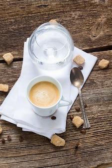 Een witte kop met verse espressokoffie en een glas water