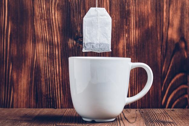 Een witte kop thee met een theezakje