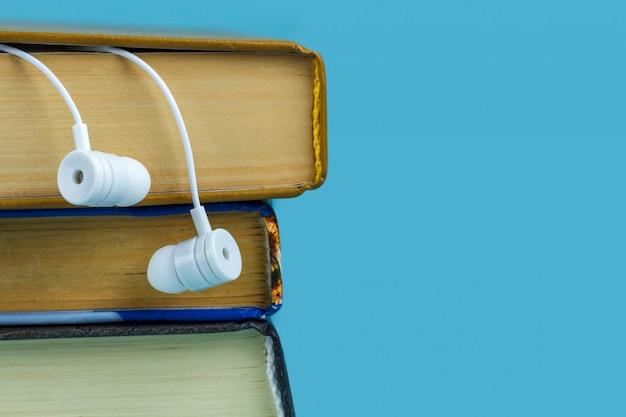 Een witte koptelefoon en boeken. audioboek concept.