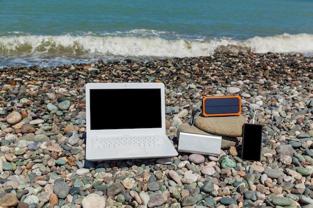 Een witte laptop ligt op rotsen in de buurt van de kust. laptop op het grind.
