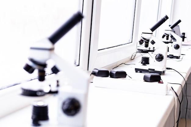 Een witte microscoop op tafel een wetenschappelijk laboratorium laboratorium van medische wetenschappen doorkijk