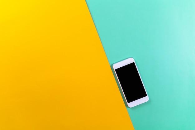 Een witte mobiele telefoon op munt en geel
