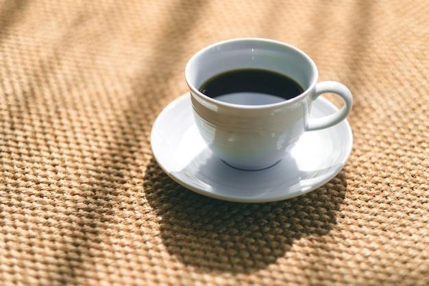 Een witte mok hete koffie op de vloerbedekking