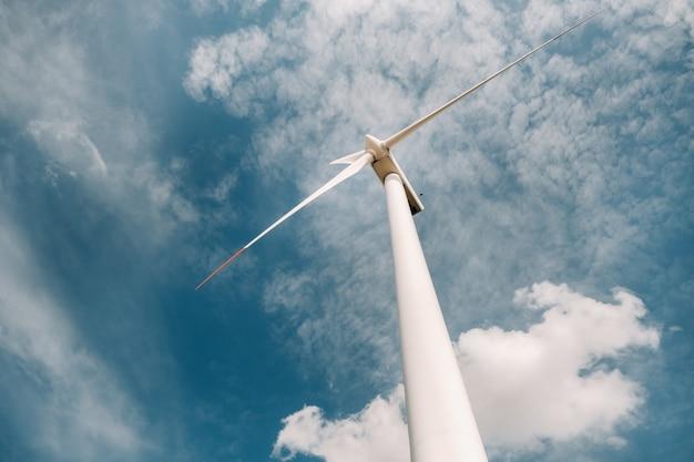 Een witte molen tegen een blauwe hemel. windmolen in de natuur.
