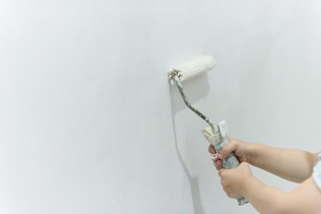 Een witte muur schilderen met een verfroller met witte verf.